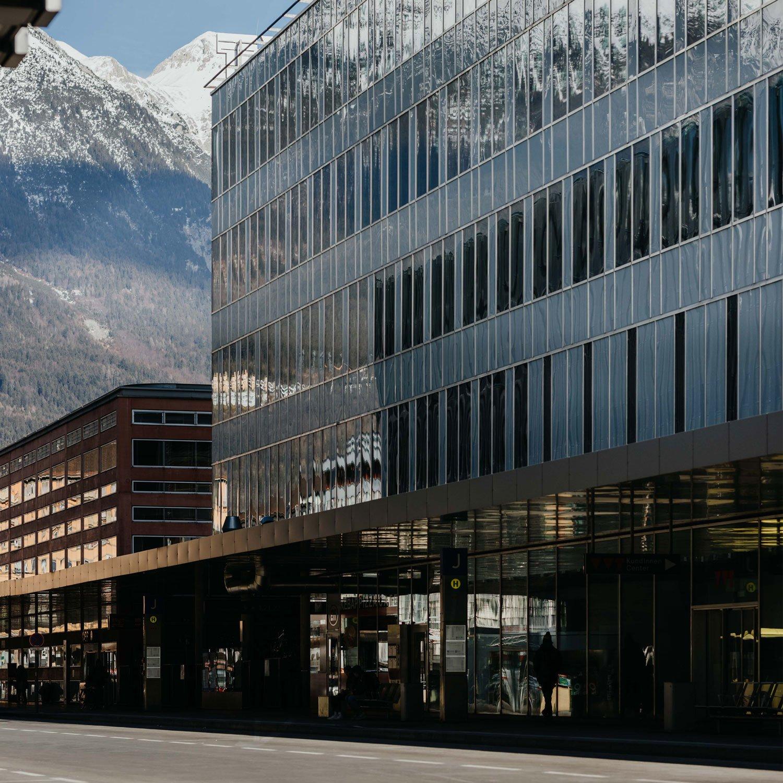 Das Bürogebäude aus den Neunzigerjahren liegt direkt am Vorplatz des Innsbrucker Hauptbahnhofs. Es besitzt eine gläserne Vorhangfassade und wird von Betonträgern über den Boden angehoben, damit auf Erdgeschossebene Busse halten können.