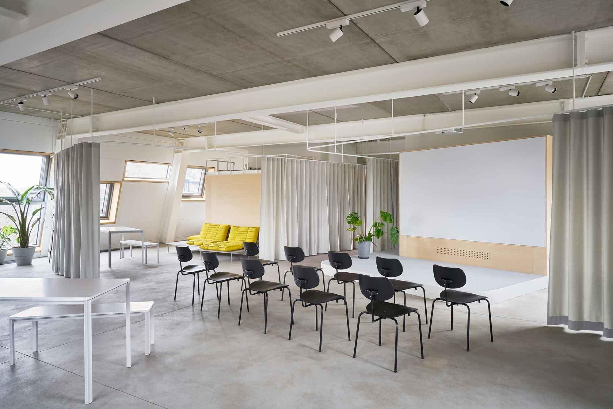 Vorhänge unterteilen den großen Büroraum und lassen verschiedene Nutzungen zu.