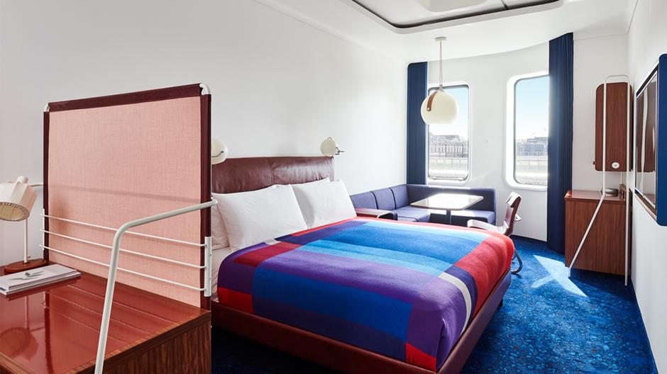Schon beim Öffnen der Türen ziehen die Bett-Überdecken mit ihren großformatigen Farbfeldern die Blicke auf sich. Der mittlere Blauton wird von den Teppichen aufgegriffen, das Dunkelblau von den Vorhängen: King's Standard Zimmer.