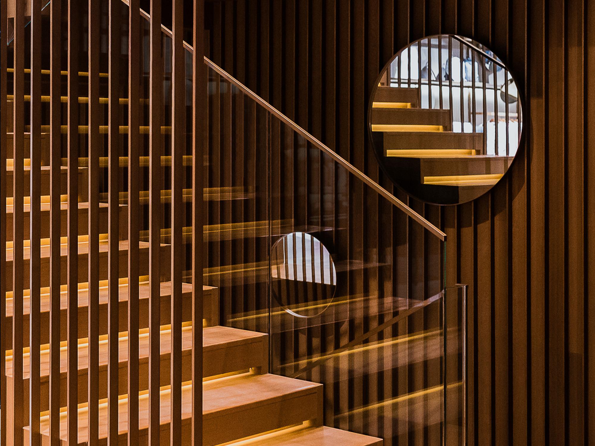 Das Treppenhausist durch einedurchlässigeEbeneaus geöffneten Bronzelamellen von den Verkaufsräumen getrennt. Foto:Dirk Weiblen © MCM