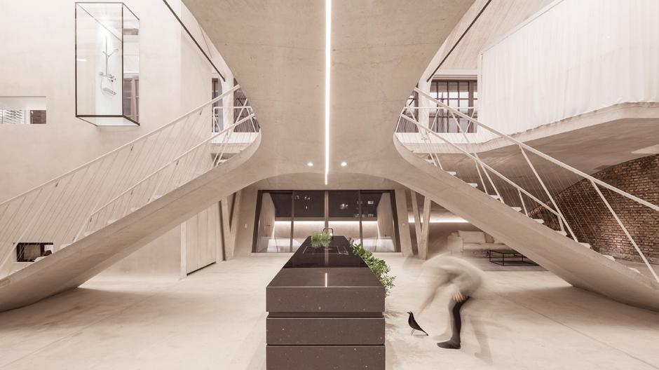 Eine geschwungene Treppe im Zentrum strukturiert das Raumgefüge...