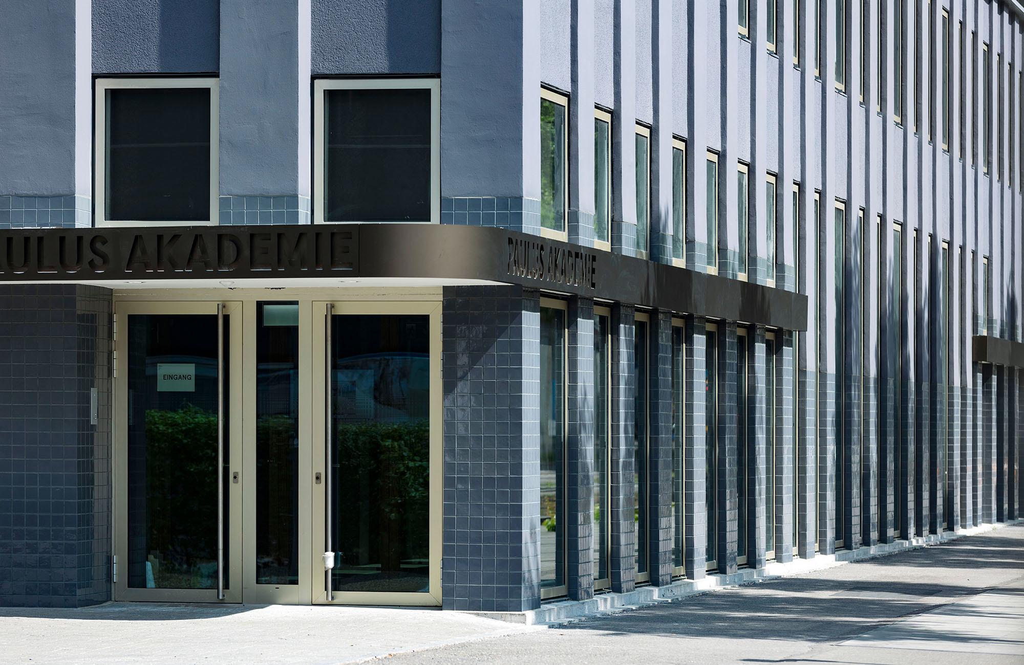 Für die Fassade der Paulus Akademie wurde eine kundenspezifische Variante unserer Kollektionsfliese PLÄTTLI entwickelt. Das Maß ist etwas kleiner und dünner, die Glasur wurde an die bestehende grau-blaue Front angepasst. © Nikolaus Spoerri
