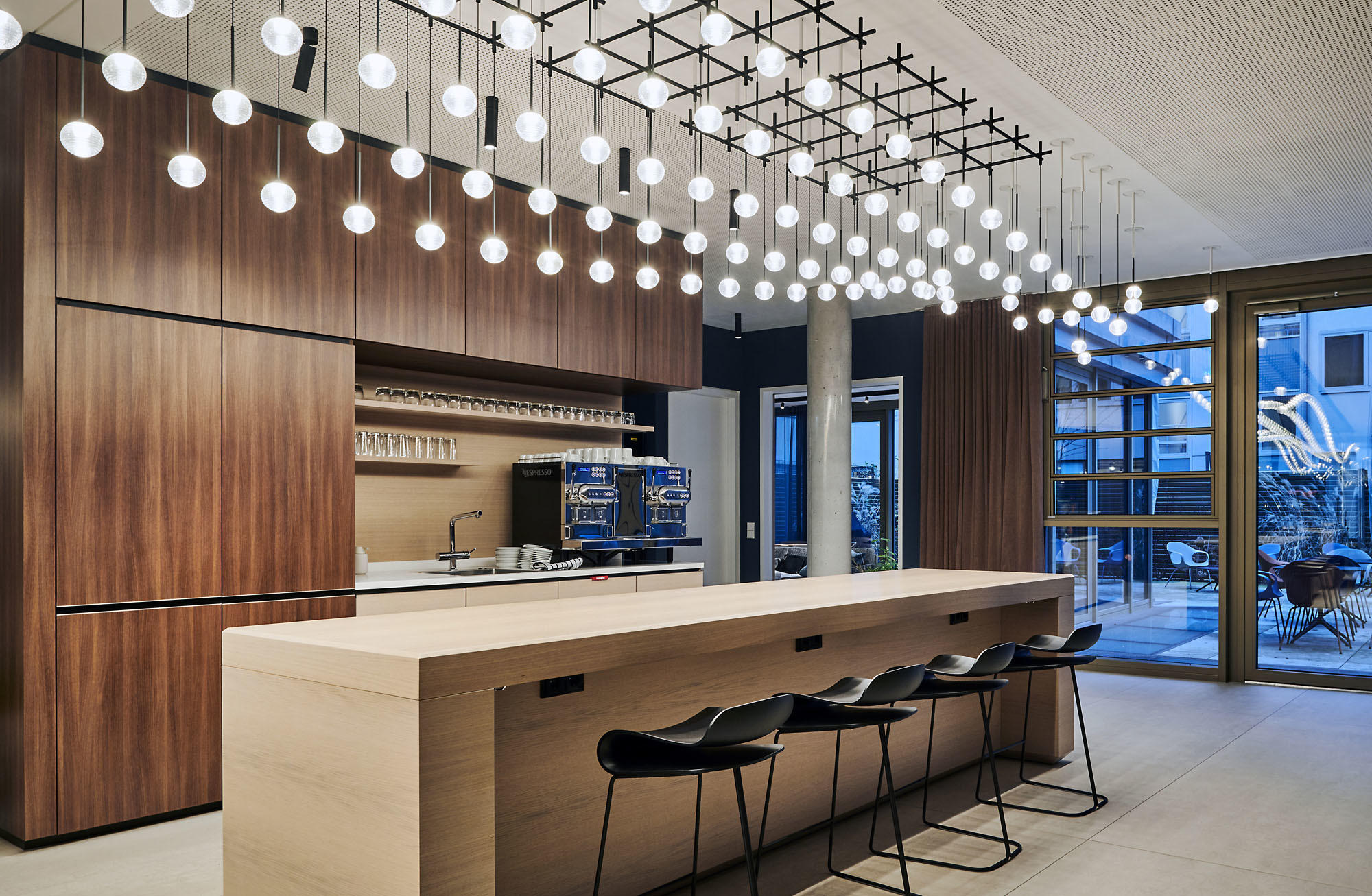 Als Ensemble bildendie Leuchtkugeln eine stilisierte Helix, die sich in dynamischer Drehung von der Eingangstür in den hinteren Teil des Gebäudes windet.