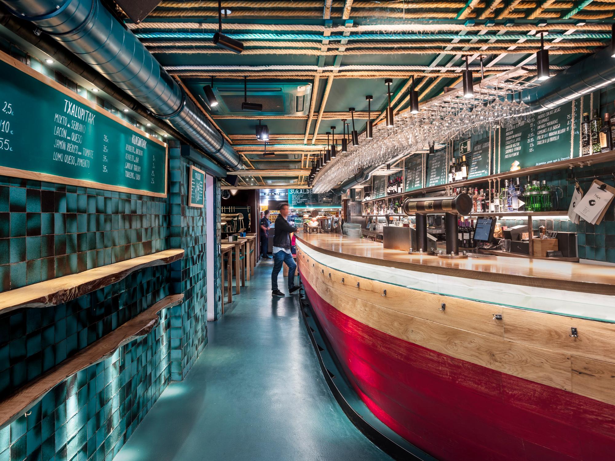 """Dergroße Tresen zieht sich vom Eingangsbereich über die gesamte Länge des Erdgeschosses. Seine Form entspricht einem halbierten Schiffsrumpf, dessen """"hölzerne Planken"""" mit einer leuchtend roten Schutzfarbe überzogen sind."""