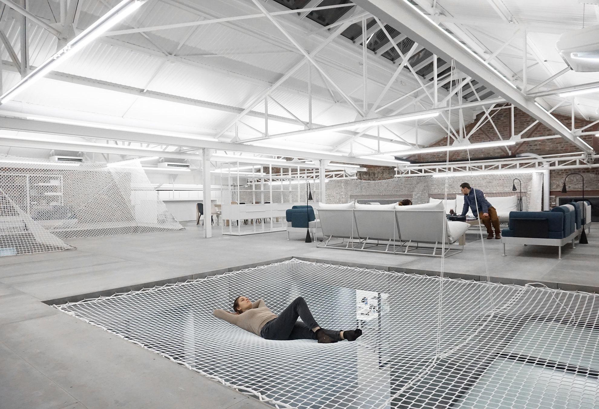 In Frankreich baute Architekt Jordan Hoareau eine Fabrikhalle in eine Zahnarztpraxis um. Dachbalken, altes Mauerwerk und Stoffnetze wurden dabei zu Blickfängern.