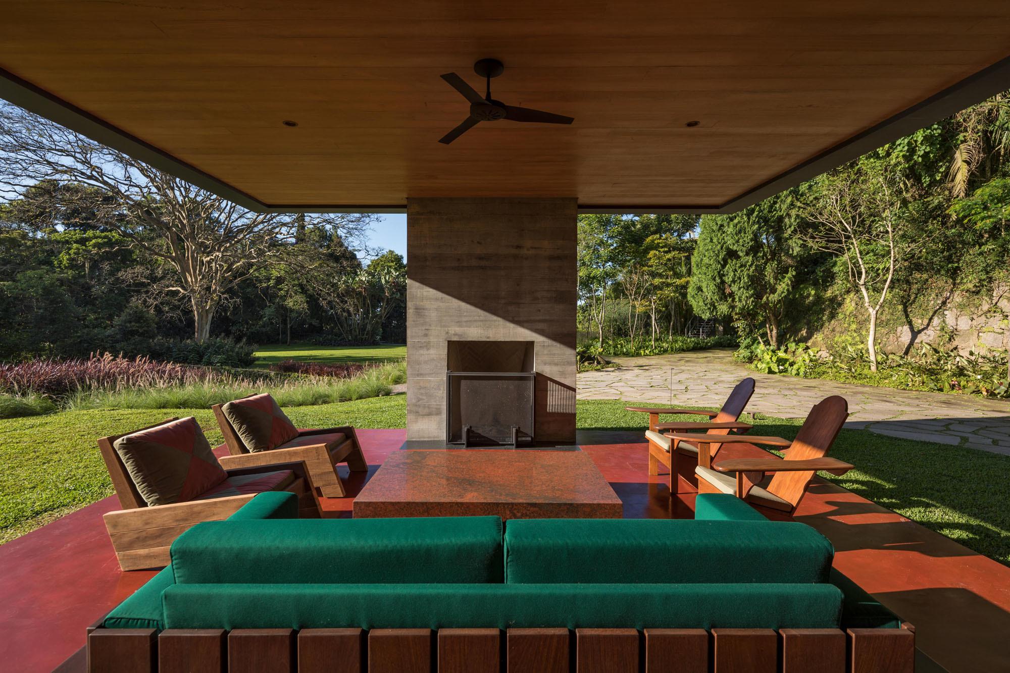 Unterhalb des schwebenden Volumens entstand ein überdachter Außenraum, der sich wiederum durch eine Bodenplatte aus Beton von den umliegenden Rasenflächen abhebt. Weder Wände, Schiebetüren, Fenster noch Vorhänge schirmen diesen Bereich von der Natur ab.