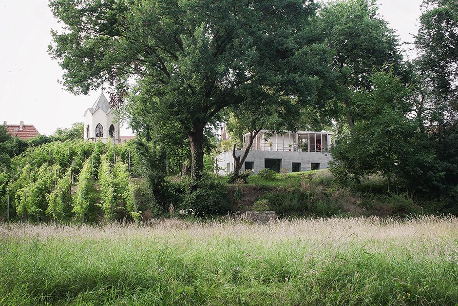 Angrenzend an einem kleinen Weinberg in der Stadt Werder liegt das Wohnhaus, das aus einem Betonquader besteht, auf dem ein Sommerpavillon sitzt.