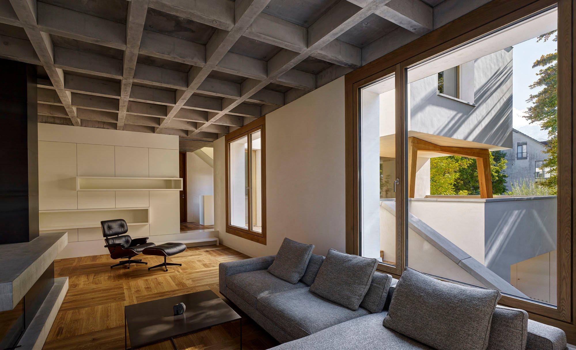 Im Wohnzimmer greift ein mit grauer Wolle bezogenes Ecksofa die Farbigkeit der Sichtbetondecken auf. Stauraum wird in maßgefertigten Schränken geschaffen.