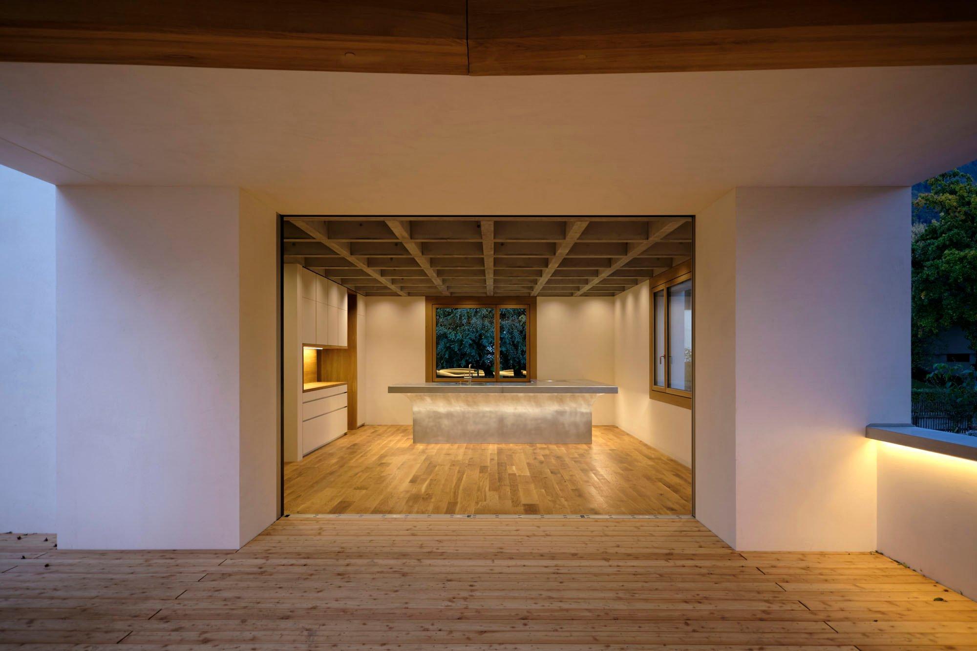 Blick von der Terrasse in die Küche: Das Wechselspiel aus Purismus und räumlicher Weite sorgt für eine überhöhte, beinahe sakrale Raumwirkung.