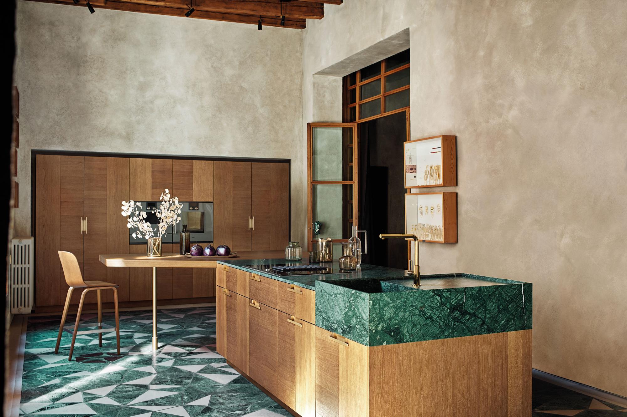 Der italienische Hersteller Cesar zeigt mit Intarsio Rovere Mediterraneo eine Küche, die Holzfurnierfronten mit Marmor Verde Guatemala kombiniert. Foto/Copyright: Cesar