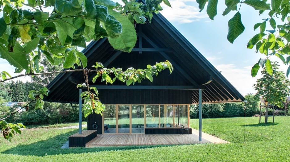 Dieses Holzhaus mit Spitzdach steht inmitten eines großzügigen Grundstücks.