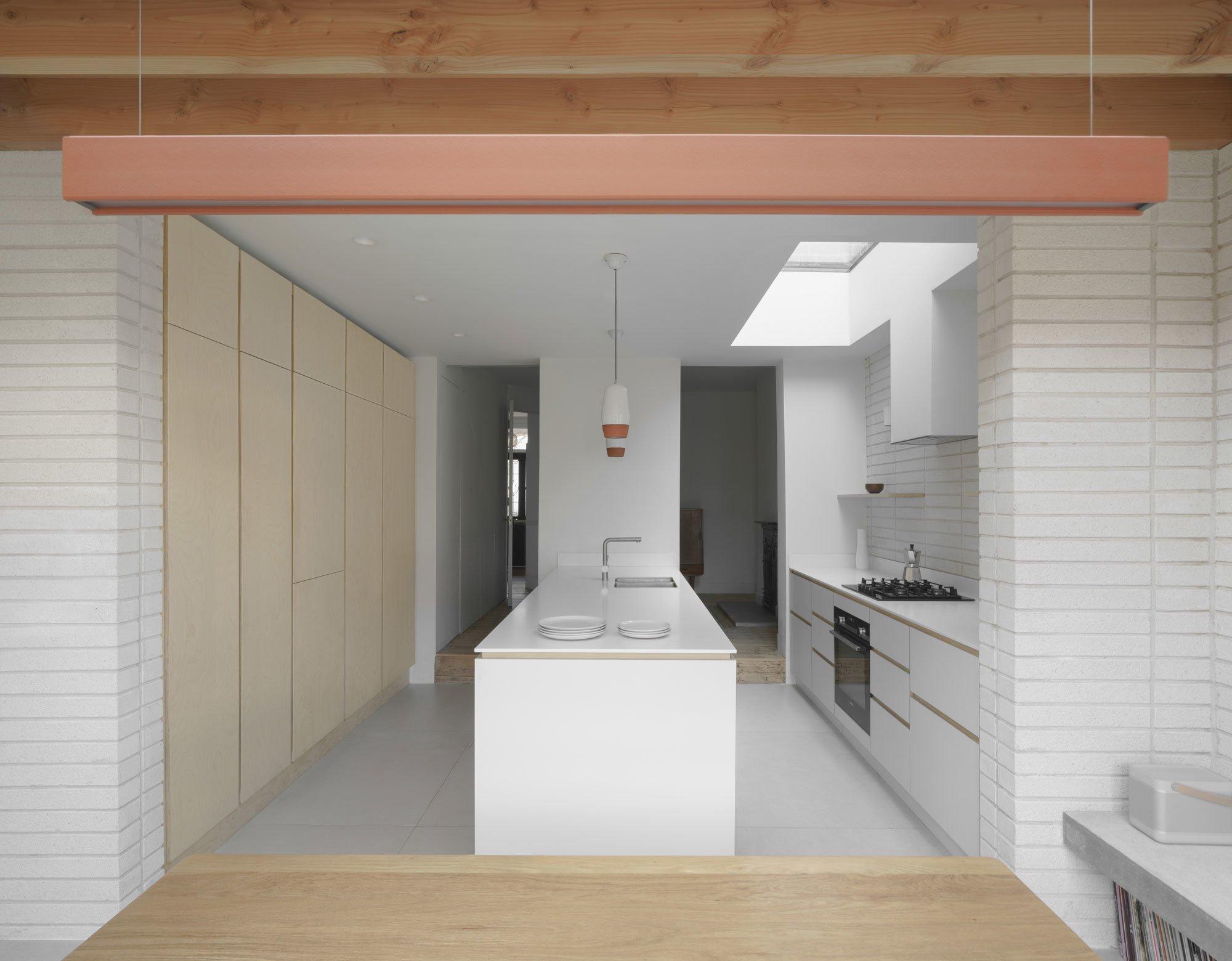 Die maßgefertigte Küche aus Birkenholz erstreckt sich über die gesamte Länge des Raumes, der im lichtdurchfluteten Esszimmer mündet.