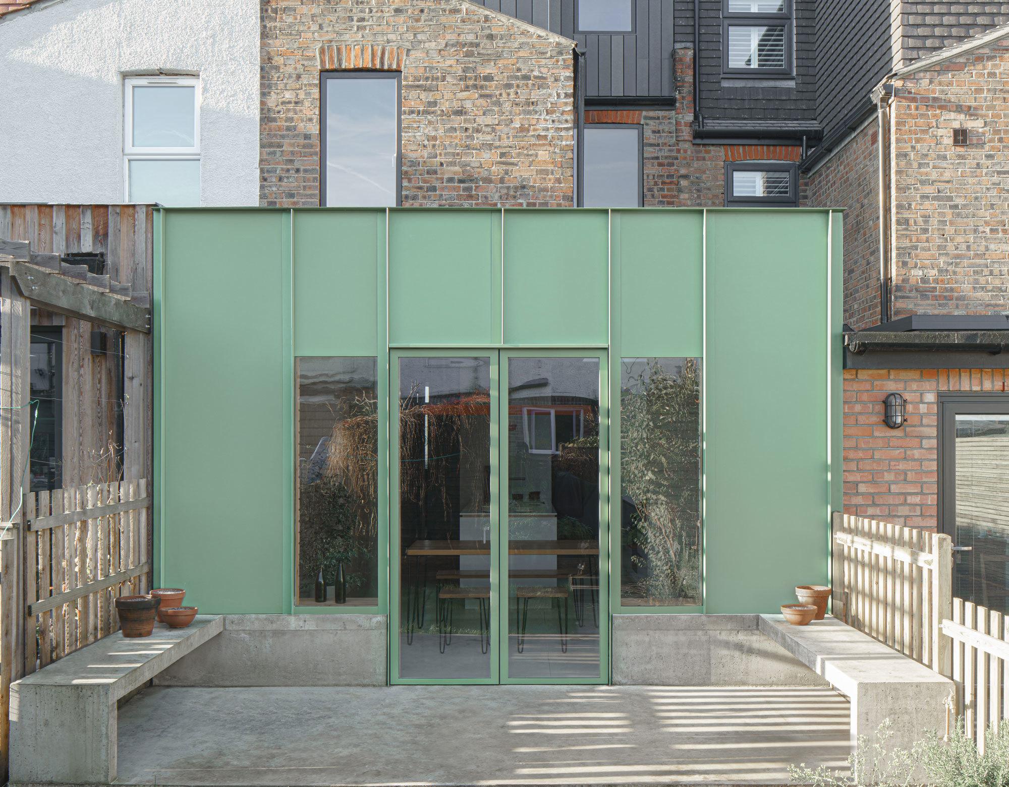 Ein Londoner Reihenhaus tanzt aus der Reihe: Die Architekten von DEDRAFT verpassten ihm einen markanten Anbau mit staubgrüner Aluminiumfassade und Betonterrasse.