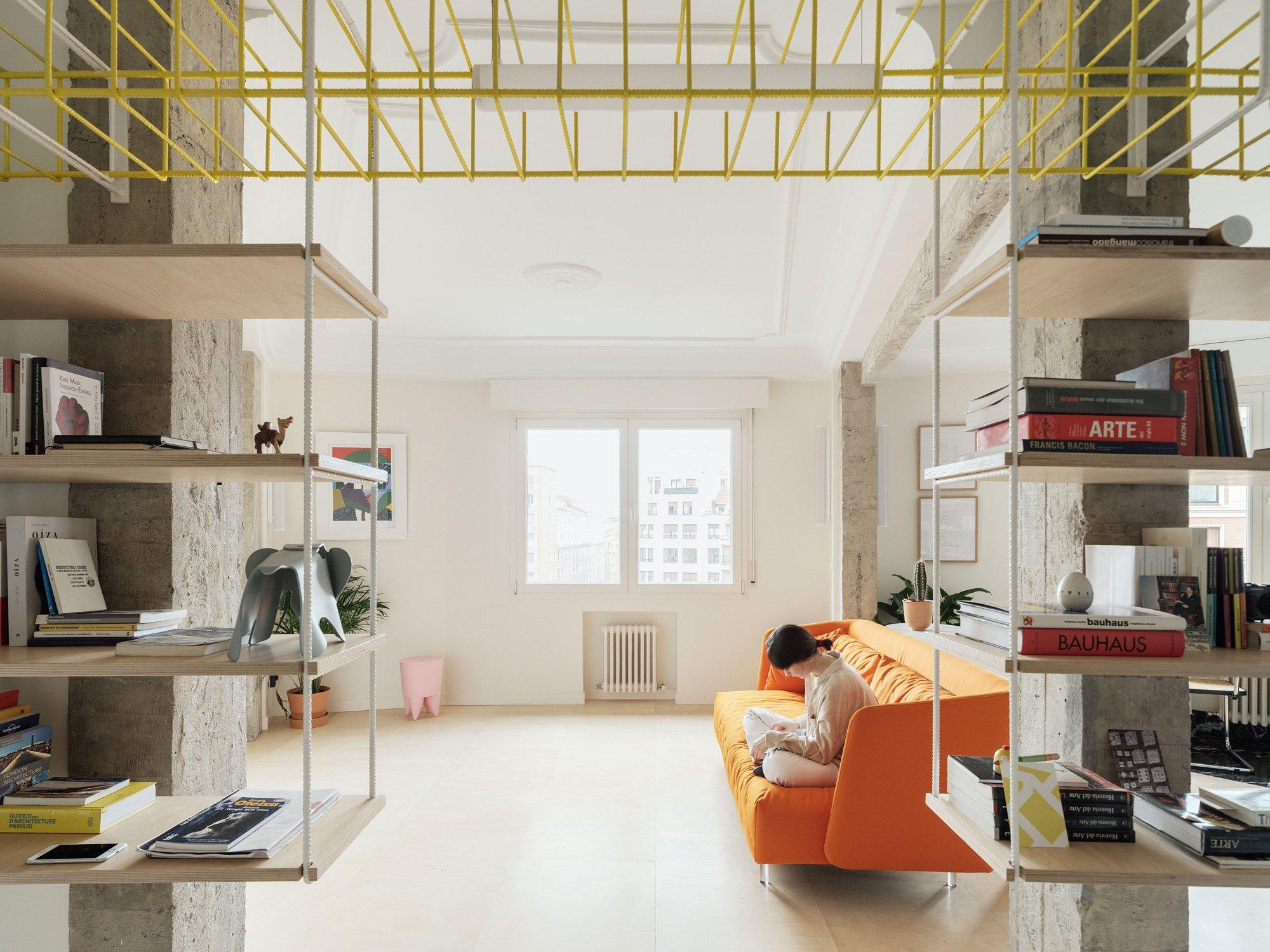 Wie das Eingangsportal zur Wohnung wirkt das eingebaute Regal aus Holz und Metall.