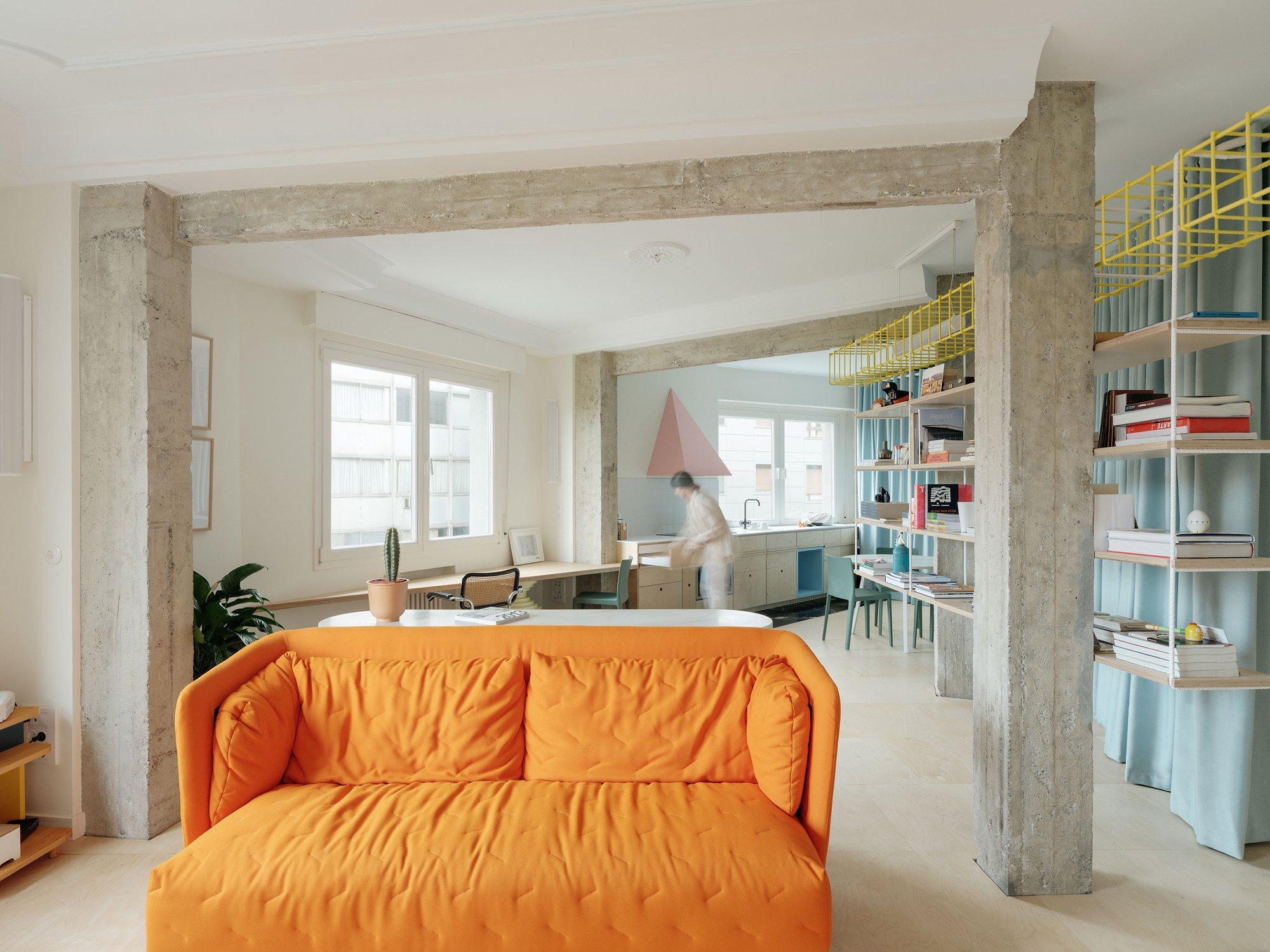 Ein Hingucker ist das orangefarbene Sofa in der Mitte des Wohnzimmers.