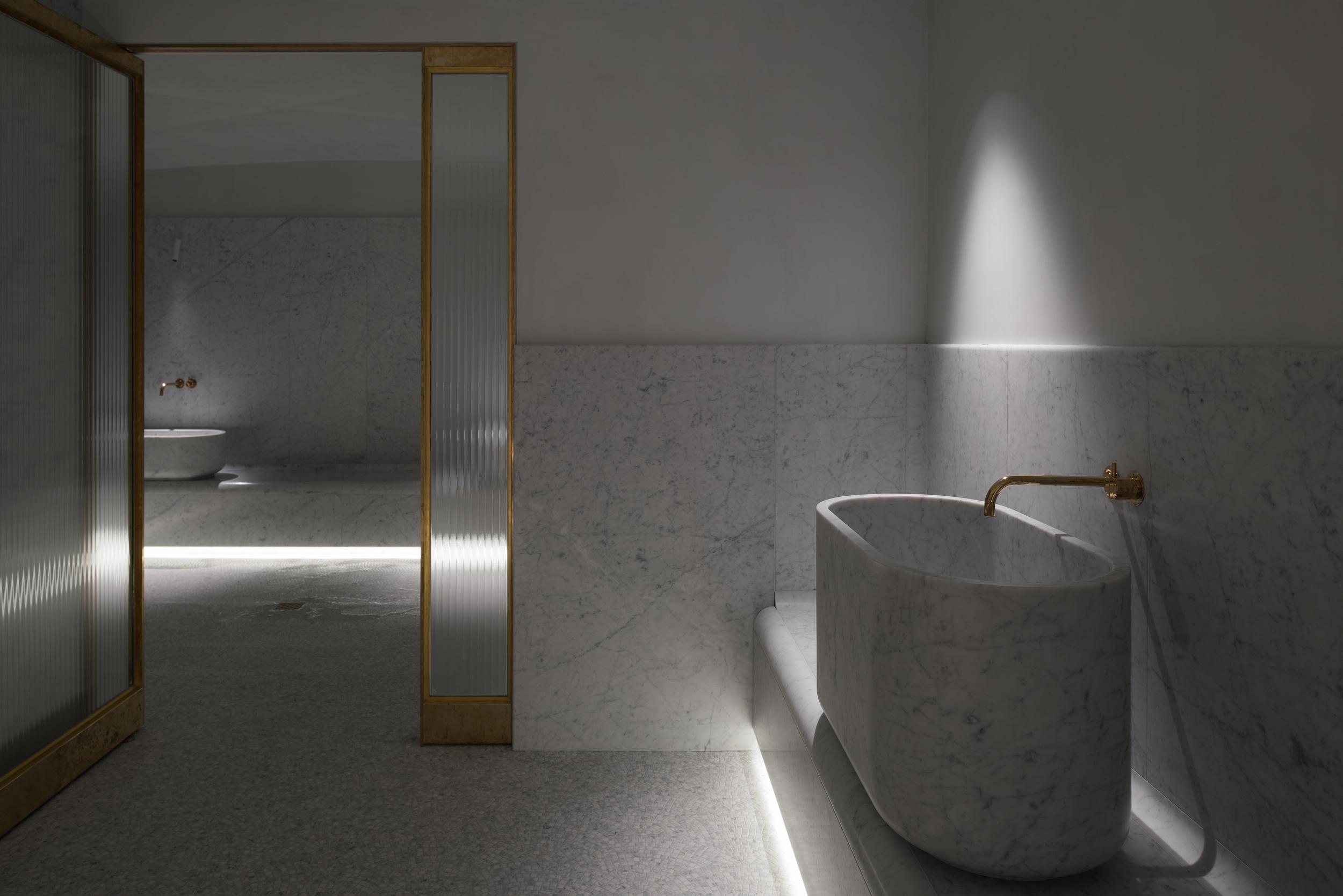 Arnold / Werner setzen auf die verbindende Materialität von Carrara-Marmor. Einen Kontrast zum weißen Natursteinerzeugenmessinggerahmte Glastüren sowie die ebenfalls aus Messing gearbeitete Armatur121X von Vola.