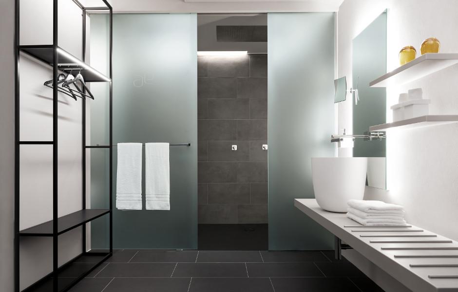 Schiebetüren aus satiniertem Glas trennen Dusche und WC-Nische voneinander und sorgen für Intimität.