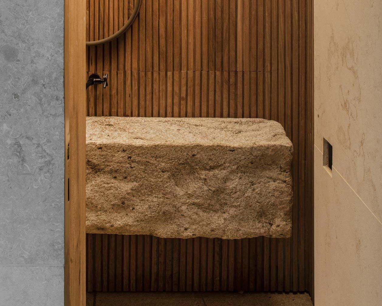In dem Ferienhaus Casa Q04L63 am Rio Grande von mf+ Architectos spielten die Architekten mit Bezügen zwischen innen und außen, indem sie sich für ein Waschbecken aus Granit entschieden. Foto: Felipe Araújo