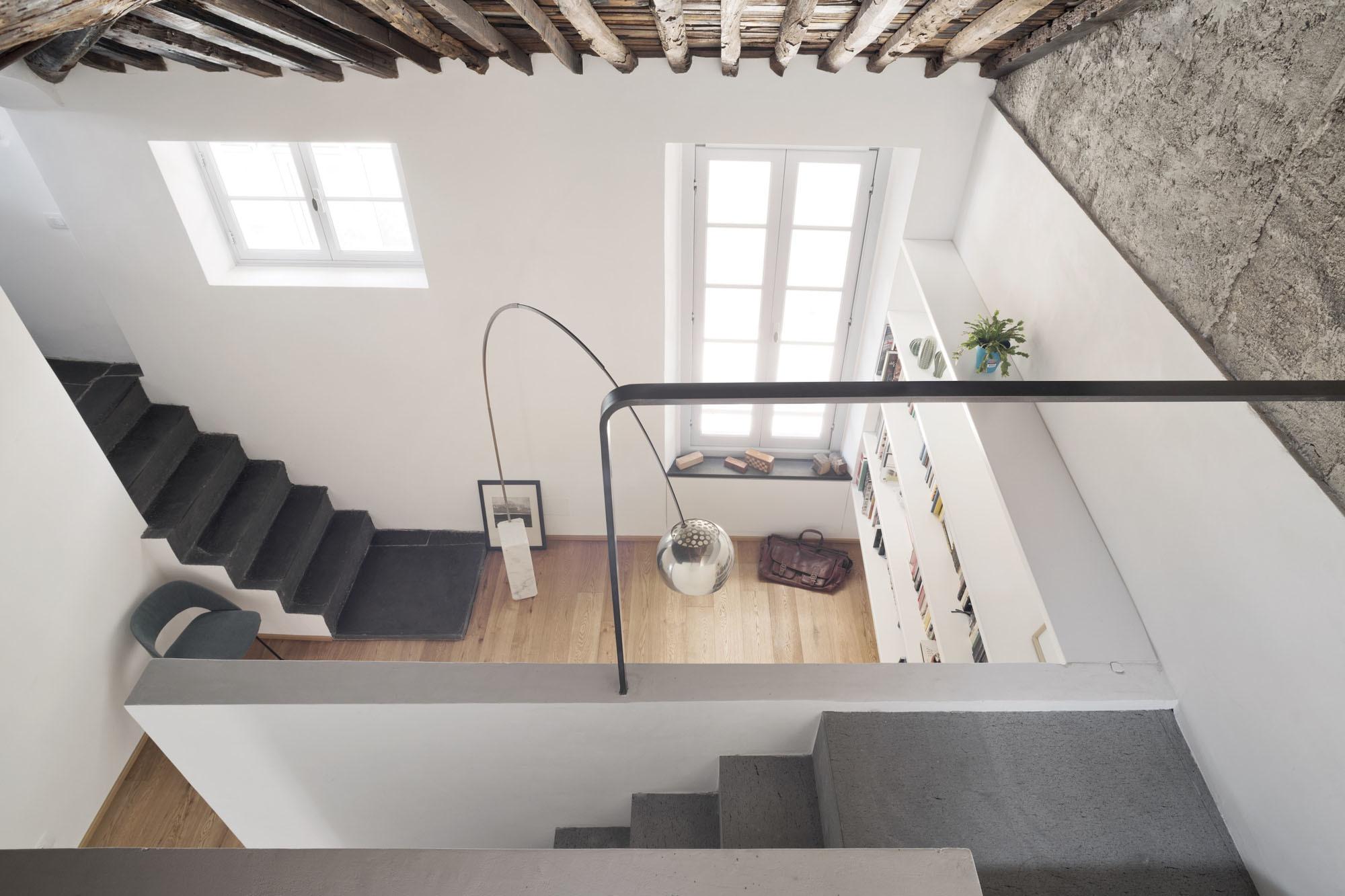 In Genua hat das Büro Dodi Moss zwei Dachgeschossein eine 110-Quadratmeter-Wohnung verwandelt: mit exponiertem Gebälk und Piranesi-artigen Raumwindungen. Links die Treppe, die von der Küche hinab in den Wohnbereich führt. Vorne rechts die Treppe, die die erhöhte Bett-Ebene erschließt.