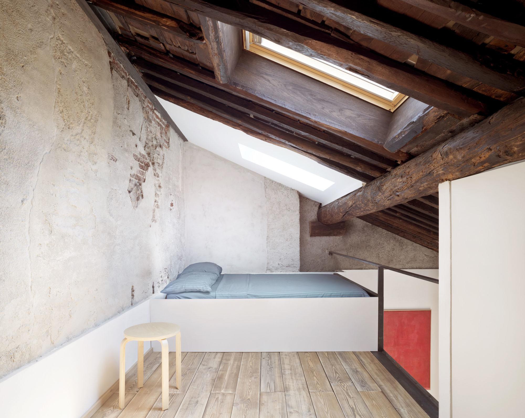 Die Architekten nutzten die Höhe des offenen Dachstuhls, um das Bett auf einer neu hinzugefügten Ebene zu platzieren.