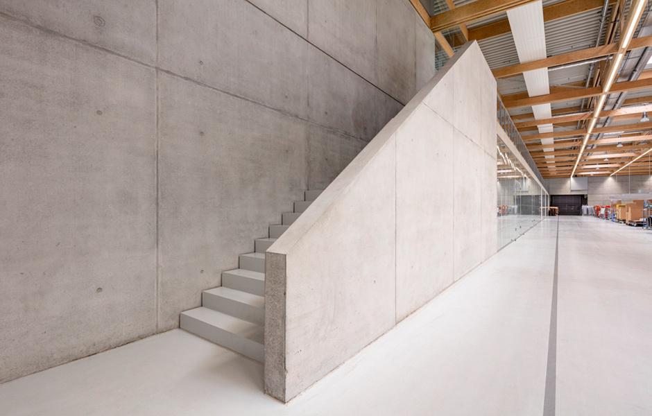 Eine klare und funktionale Architektursprache trifft auf warme Materialien, wie das Holztragwerk.