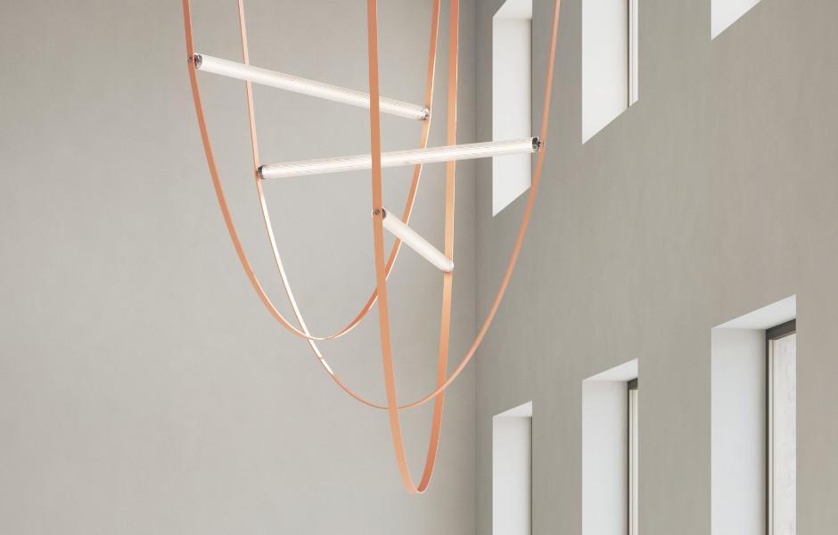 Der der Pendelleuchte WireLine von Formafantasma für Flos fungiert auch das Stromkabel als formgebendes Element. Dabei hängt das abgeflachte, einem Gürtel aus Gummi ähnelnde Kabel u-förmig von der Decke und spannt beidseitig eine gerippte Glasröhre mit einer LED-Lichtquelle ein.