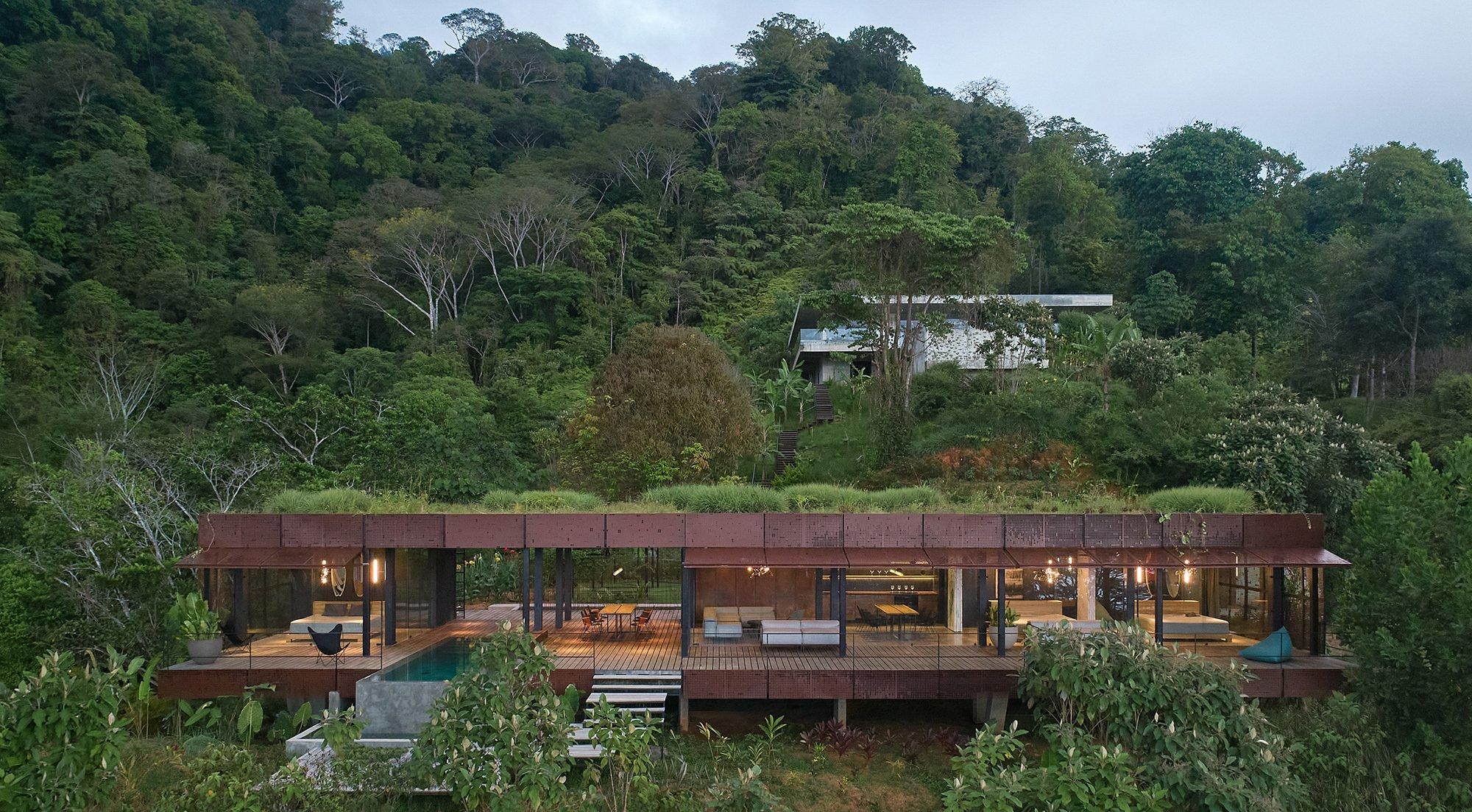 Das Haus löst die Grenzen zwischen Drinnen und Draußen, zwischen Natur und Wohnraum auf. Das perforierte Wandmodul wird als Flügel zum temporären Schattendach.
