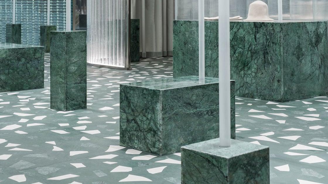 Auf dem Terrazzo-Boden sind kubische Sockel aus grünem Marmor platziert, die in Höhe und Breite variieren und zum Teil zur Präsentation von Accessoires und Kleidungsstücken dienen.
