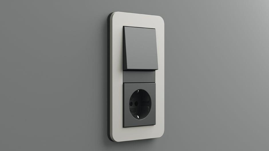 Gira E3 mit Soft-Touch-Oberfläche in Grau, Tastschalter und SCHUKO-Steckdose im Farbton Anthrazit.