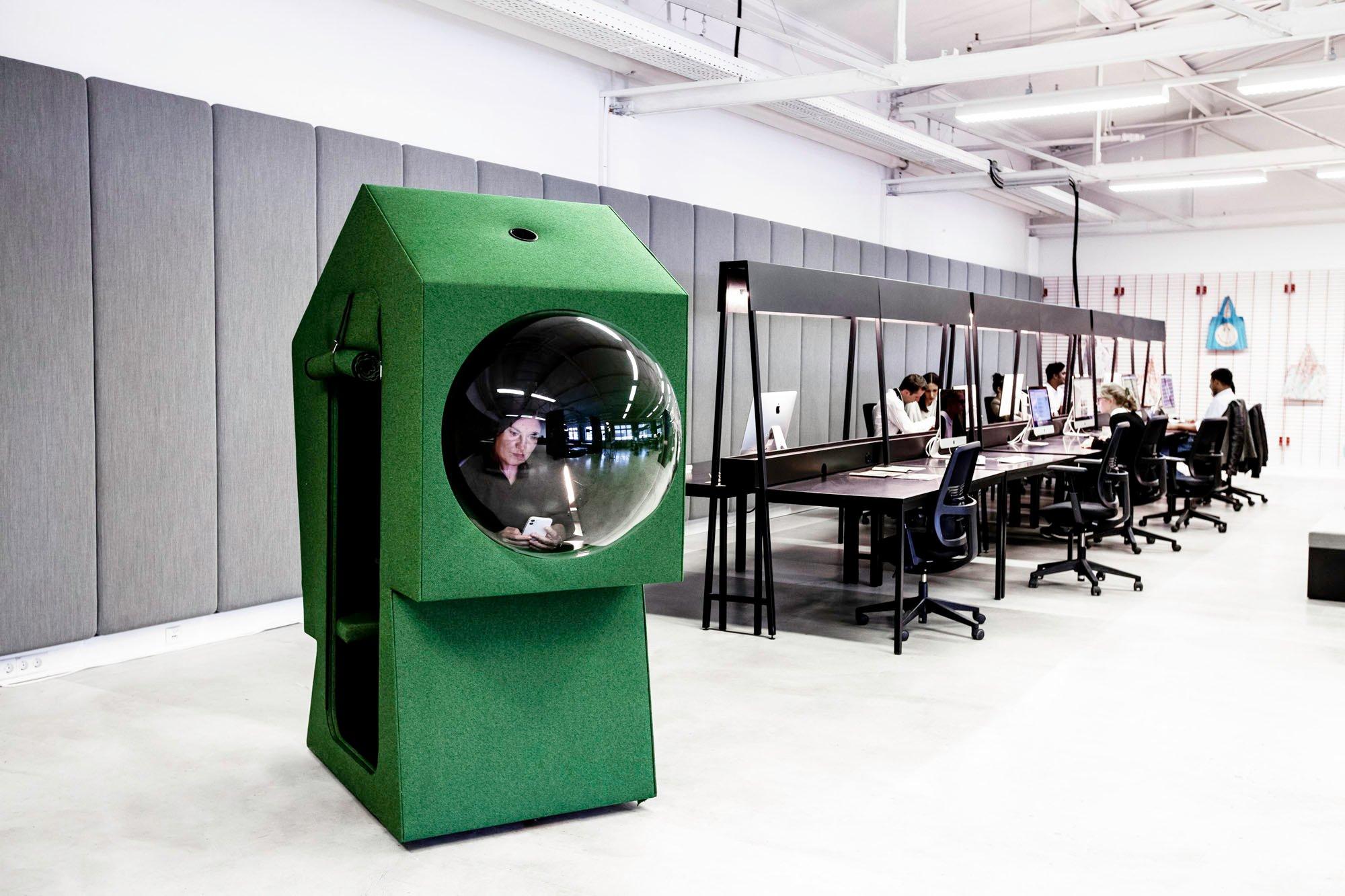 Monochrom in grün oder blau gehaltene Work Capsules stehen frei im Raum. Die Micro-Architekturen von Studio Aisslinger bilden einen Arbeitsplatz für eine Person mit gepolstertem Sitz und Schreibtisch.