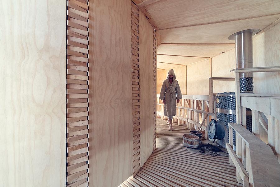 Im Saunaraum nimmt man auf Holzbänken entlang der Wand Platz.