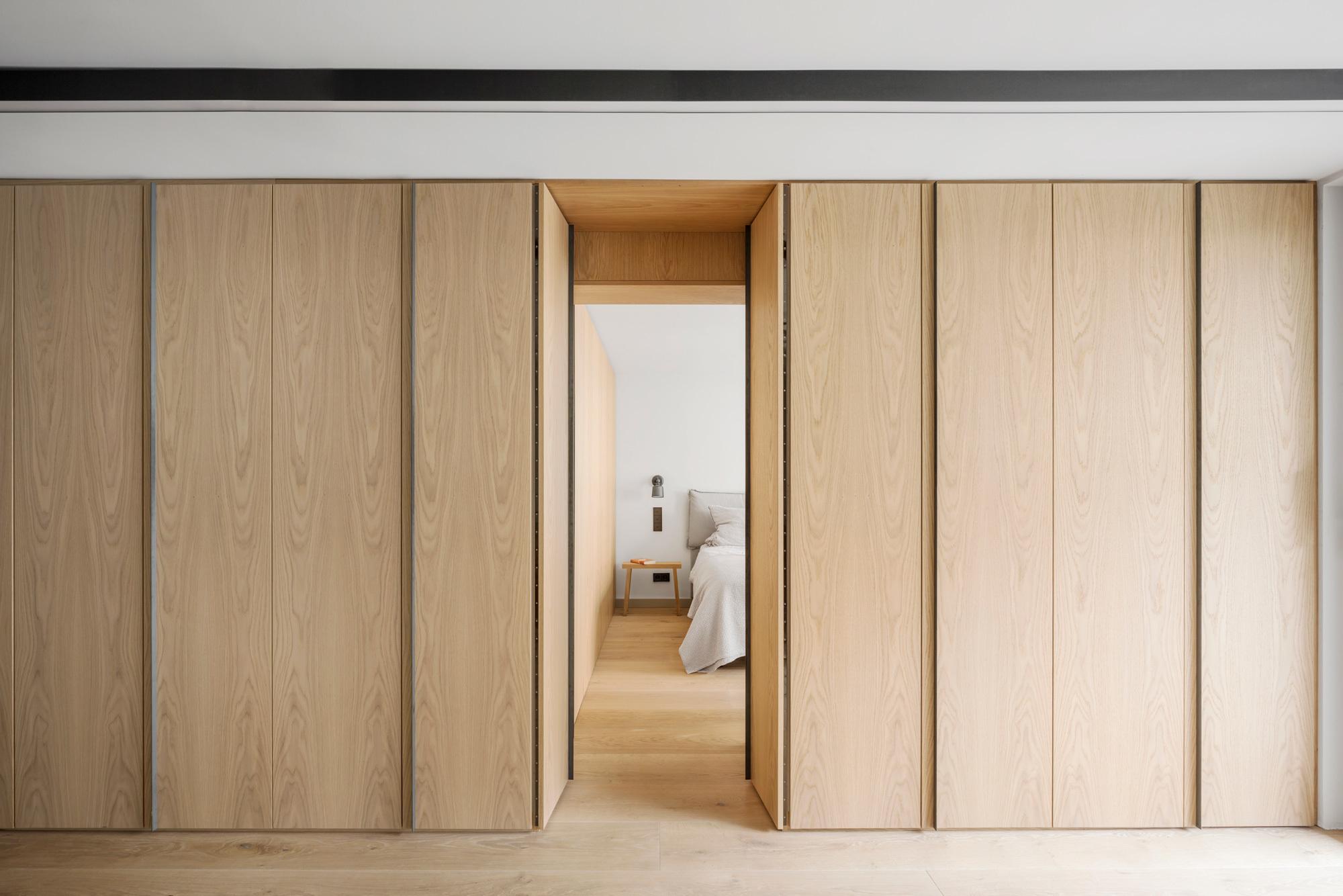 Hinter den maßgeschneiderten Möbeleinbauten aus aufgehellter Eiche liegt das Schlafzimmer.