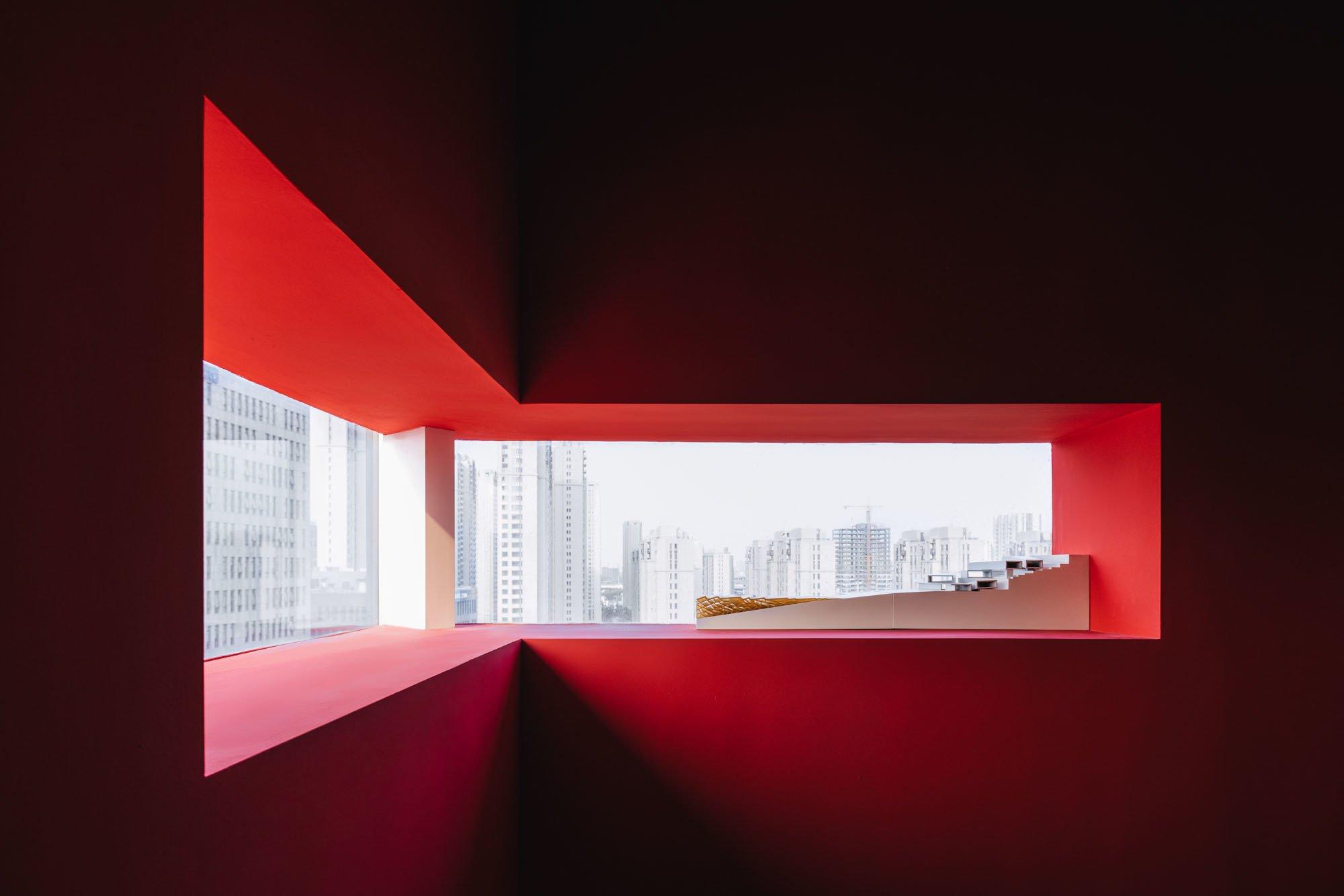 RoterOlympus-Raum: Schmale Fenster öffnen den Blick nach draußen auf die Skyline von Shanghai.