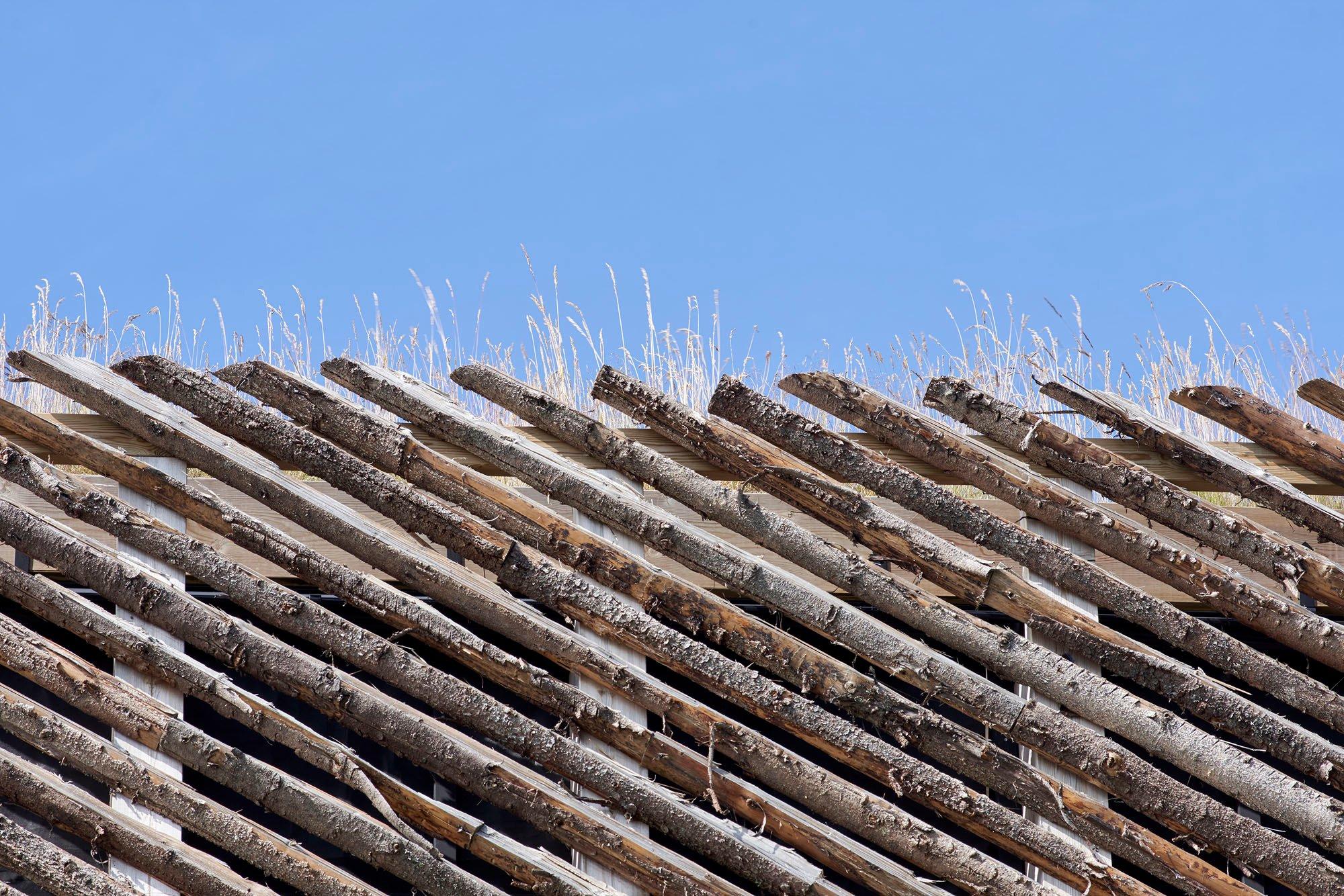 Eine vorgelagerte Zaunebene fängt die Schneemassen ab, bevor sie die eigentliche Massivholzfassadesowie die großformatigen, bodentiefen Fenster erreichen.
