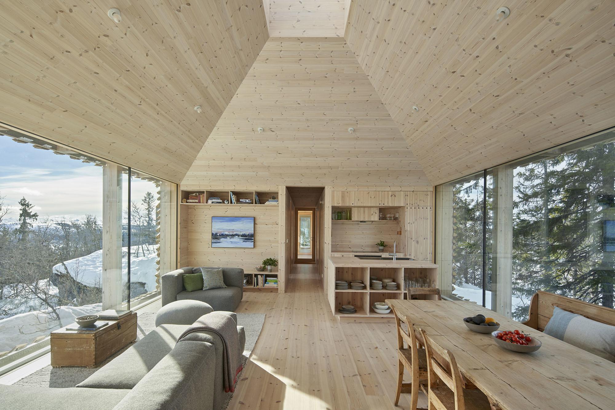 Bodentiefe Fenster öffnen die Innenräume beidseitig nach außen – mit Blick auf die umliegenden Berggipfel und zahlreichen Nadelbäume.