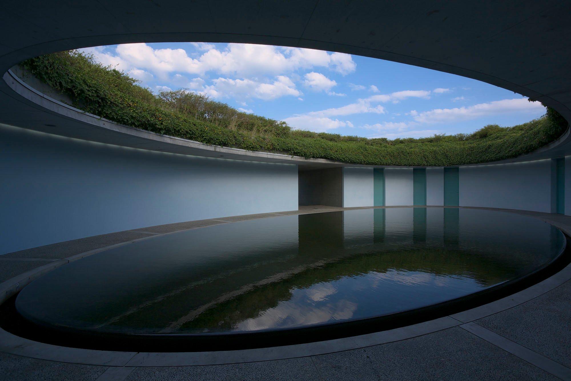 Hotels sind mehr als Übernachtungsstätten. Sie sind räumliche Erlebnisverstärker. Manchmal geht ihre Wirkung so weit, dass sie selbst zur Destination werden. Im Bild: BENESSE HOUSE: Im Sichtbetonbau Oval gruppieren sich sechs Zimmer um einen ovalen Innenhof mit Wasserbecken, der ins Erdreich eingelassen ist und sich zum Himmel öffnet. Foto: Osamu Watanabe / Benesse House