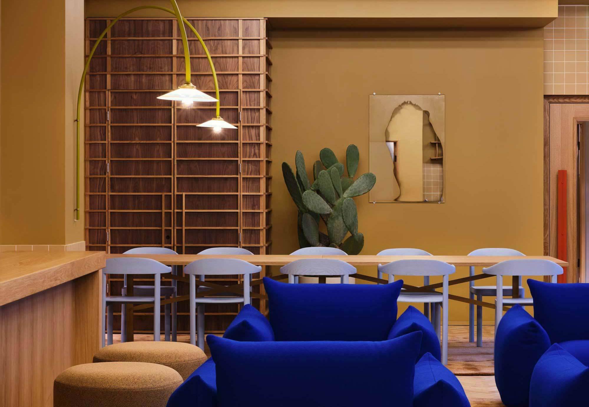 Mit mutigen Materialkombinationen denken Note Design Studio im Londoner Douglas House Bürowelten neu. Kobaltblaue Sessel bilden einen farbigen Kontrast zu den Naturtönen der Räume.