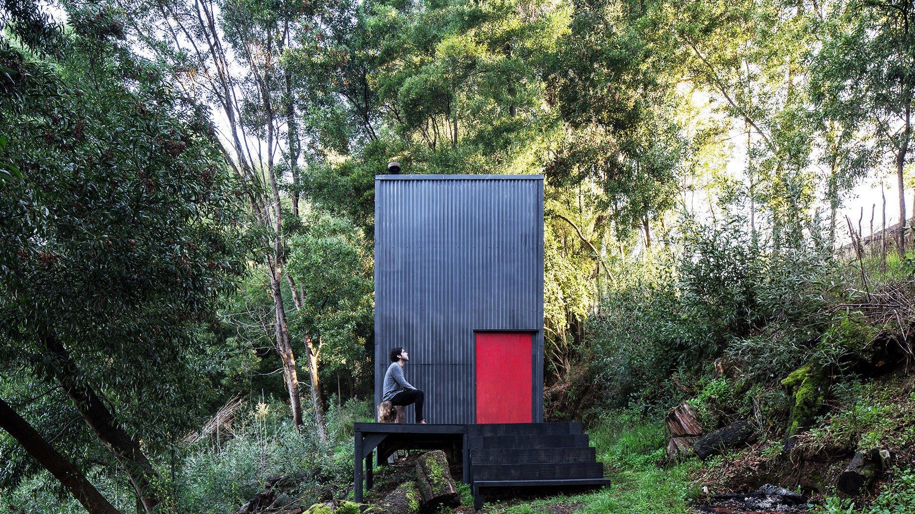 Die drei Meter im Quadrat große Hütte tarnt sich im Unterholz mit einem dunklen Anstrich. Die weithin sichtbare, signalrote Tür markiert ihren Eingang.