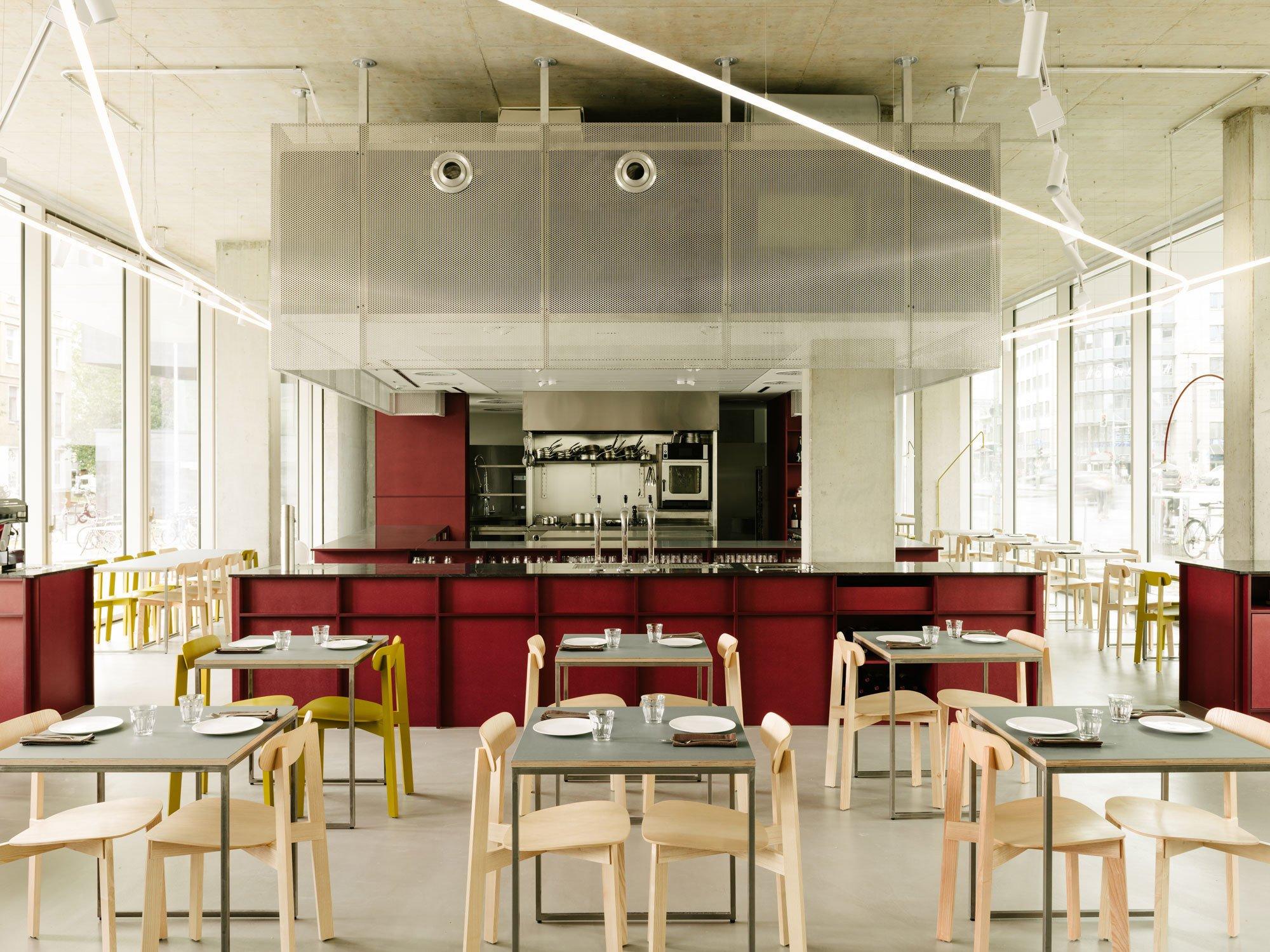 Zwei Fensterfronten öffnen das Restaurant mit bodentiefen Scheiben zur Stadt. Zwischen beiden Seiten spannt sich eine offene Küche mit Korpussen aus rotem MDF.