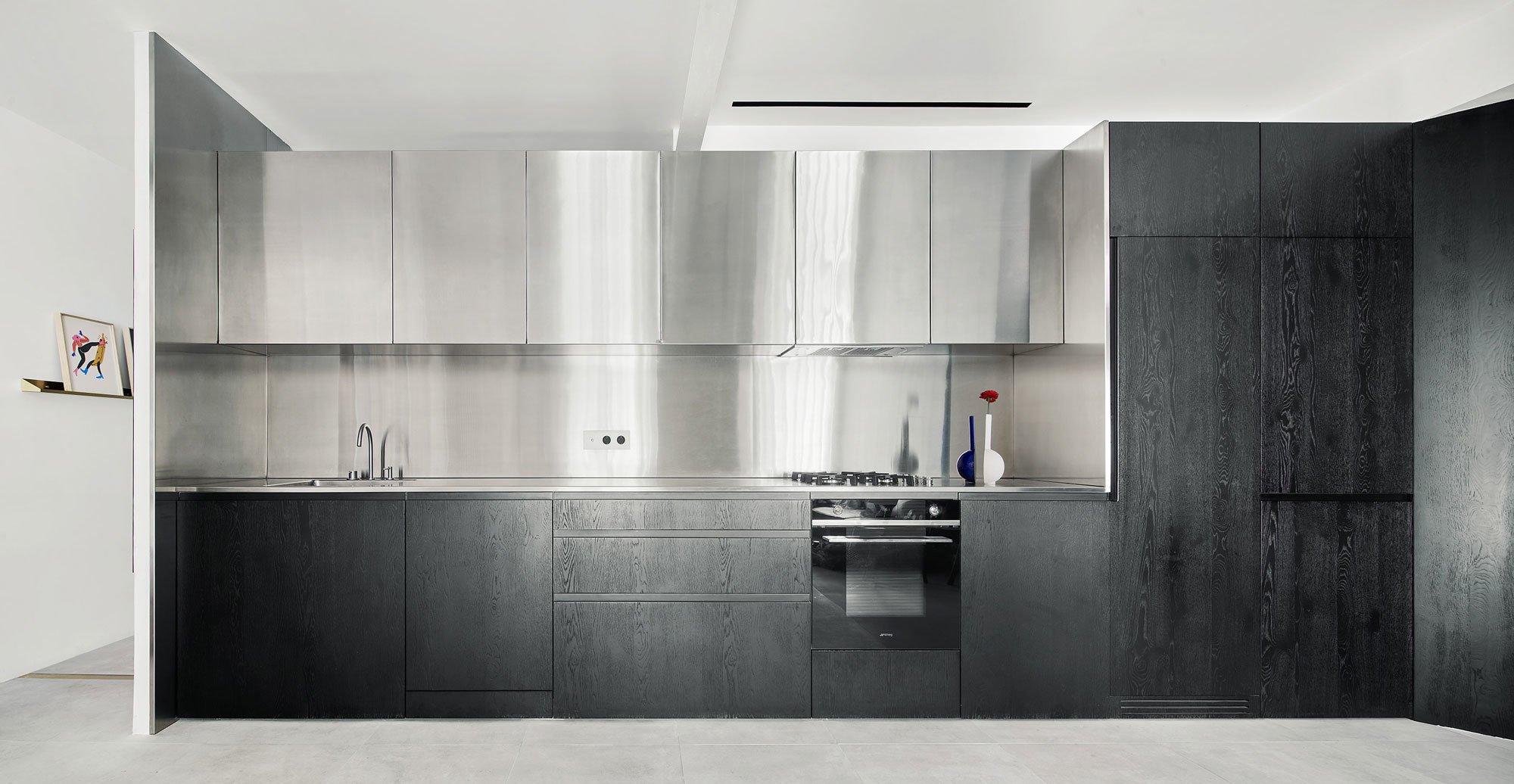 Die unteren Fronten der Küche sindmit offenporigen, schwarz gestrichenen Eichenholzpaneelen verkleidet. Für die darüber liegenden Schranktüren sowie die Rückwand wird Edelstahl verwendet.