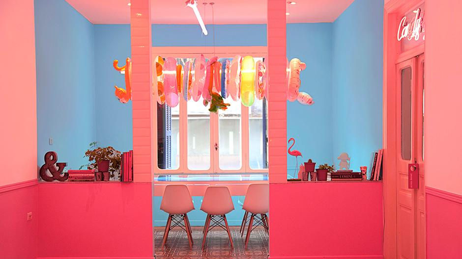 Kontrastprogramm mit Gummitieren: Über dem Konferenztisch hängen bunte Schwimmringe, während rote Wände vor blauen stehen.