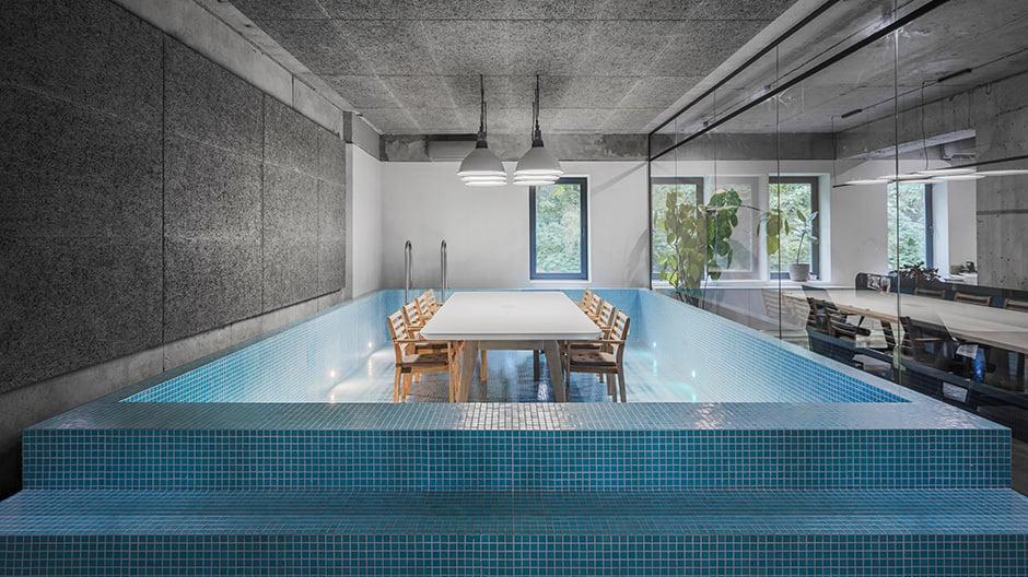 Zum Meeting in den Pool: Die Kreativagentur lässt Mitarbeiter und Besucher über eine Leiter an den großen Tisch kommen.