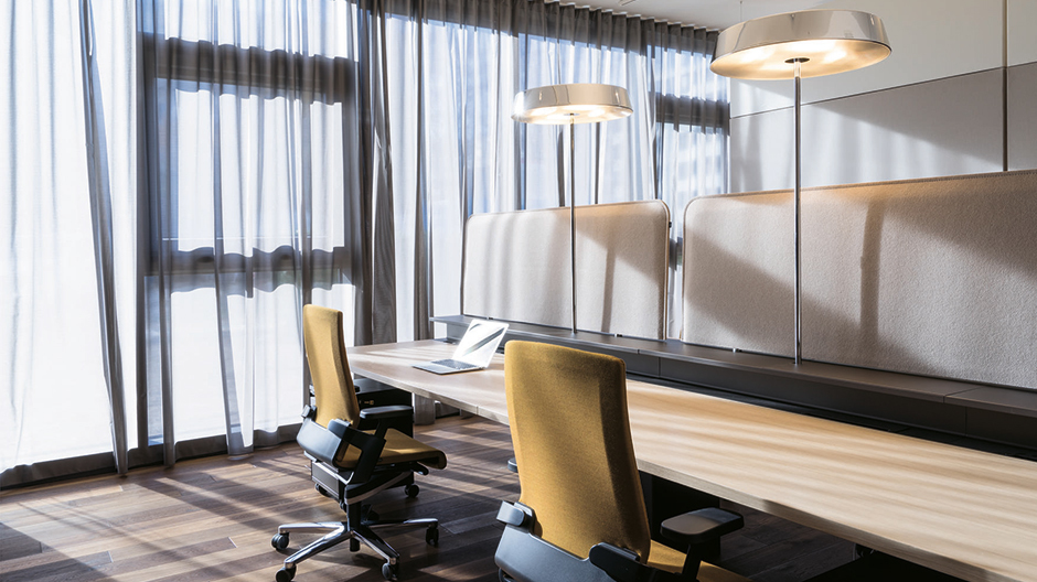 Sanfte Nuancen und ein warmes Lichtkonzept machen die Arbeitsplätze zu gemütlichen Orten der Achtsamkeit.