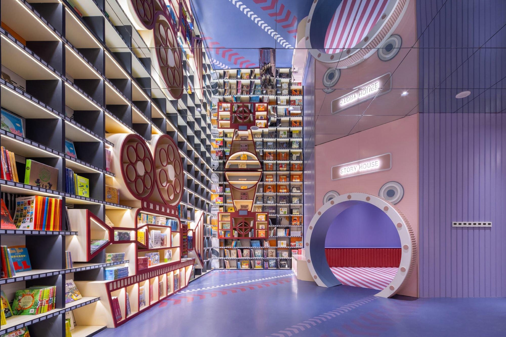"""Auf dem hellblauen Turnhallenfußboden der Kinderspielecke weisen die grafischen Markierungen einer Filmklappe in ein separates Spielzimmer mit der Aufschrift """"Story House""""."""