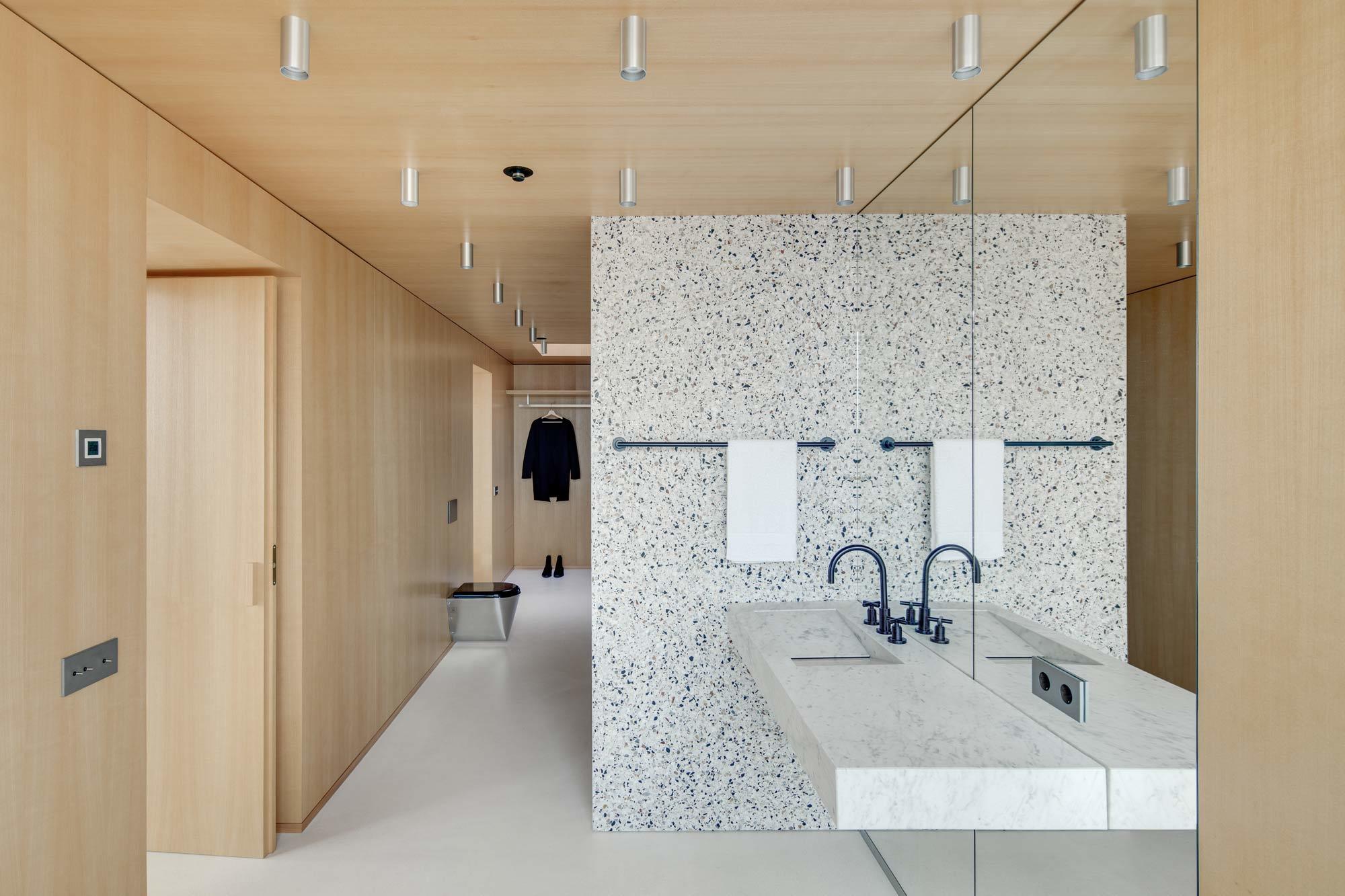 Ein Traum für Terrazzo-Fans ist die Wohnung von DO Architects in Litauen. Nicht nur im Wohnzimmer, auch im Bad zeigt sich die Freude an dem Material. Dort dient eine bunte Terrazzo-Wand als Sichtschutz. Foto: Norbert Tukaj