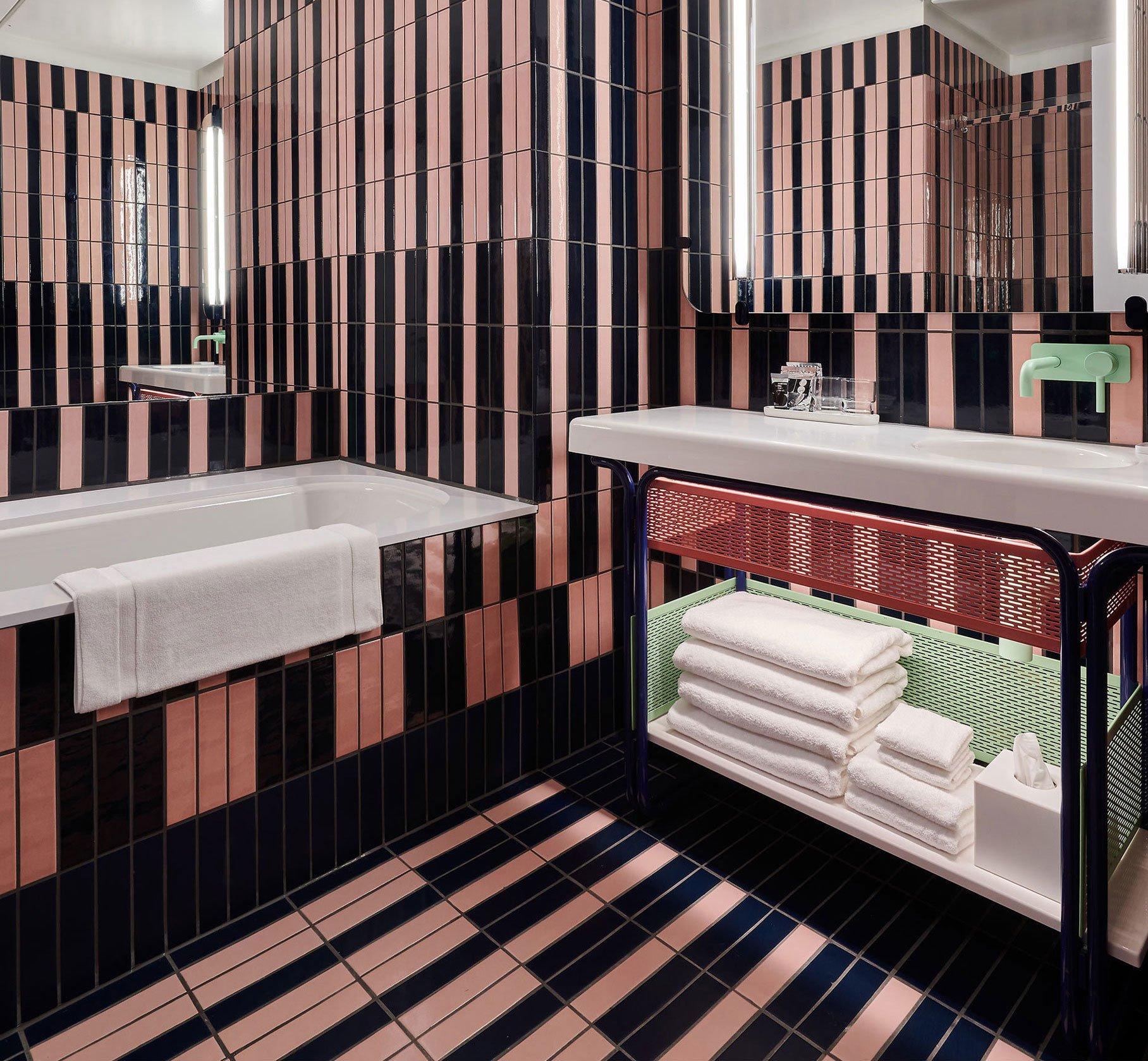 In den Badezimmern stehen farbige Fliesenmuster an Wand und Boden eleganten Badmöbeln in Weiß von Bette gegenüber – wie zum Beispiel der Wannenkollektion BetteForm.
