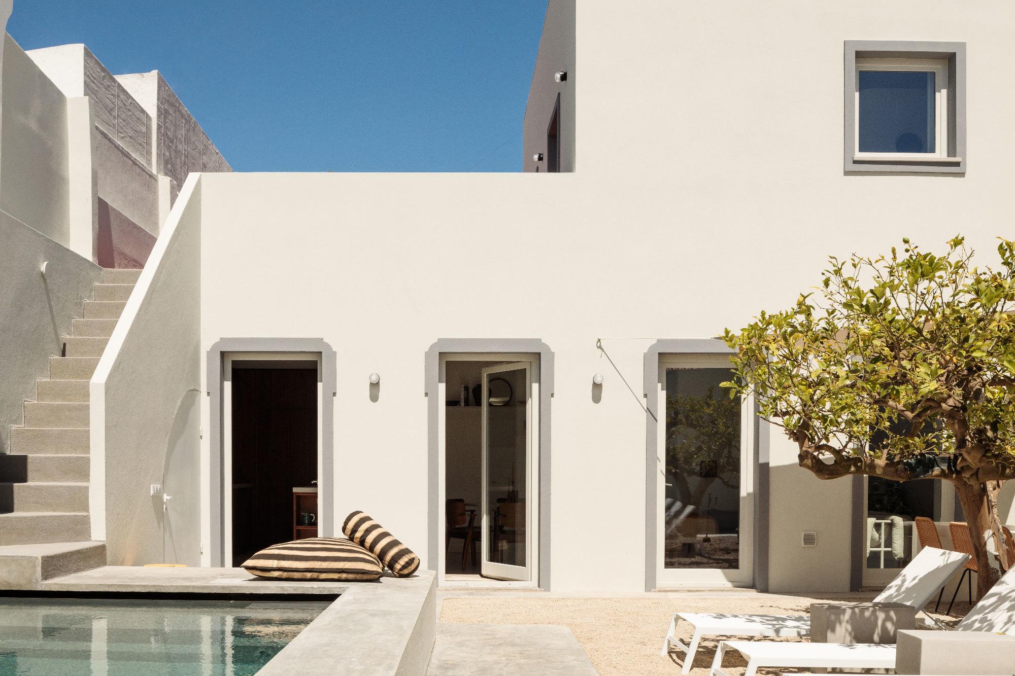 Die Wohnräume sind um einen hellen Innenhof mit einem alten Zitrusbaum gruppiert und durch große Fenster mit dem Außenbereich verbunden.