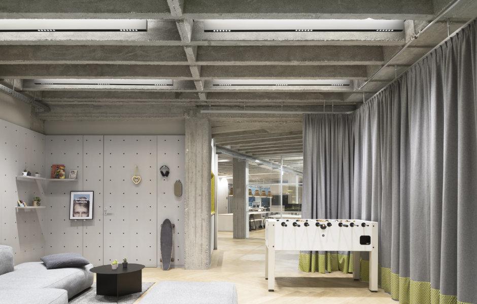Der Adaptive Space, ein großer flexibel nutzbarer Gemeinschaftsraum, kann sowohl für Pausen als auch für Vorträge, Workshops oder Büroessen genutzt und durch graue Vorhänge vom Eingang separiert werden.