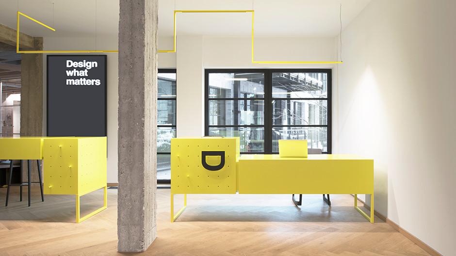 Zwei gelbe Tresen begrüßen die Kunden am Empfang.