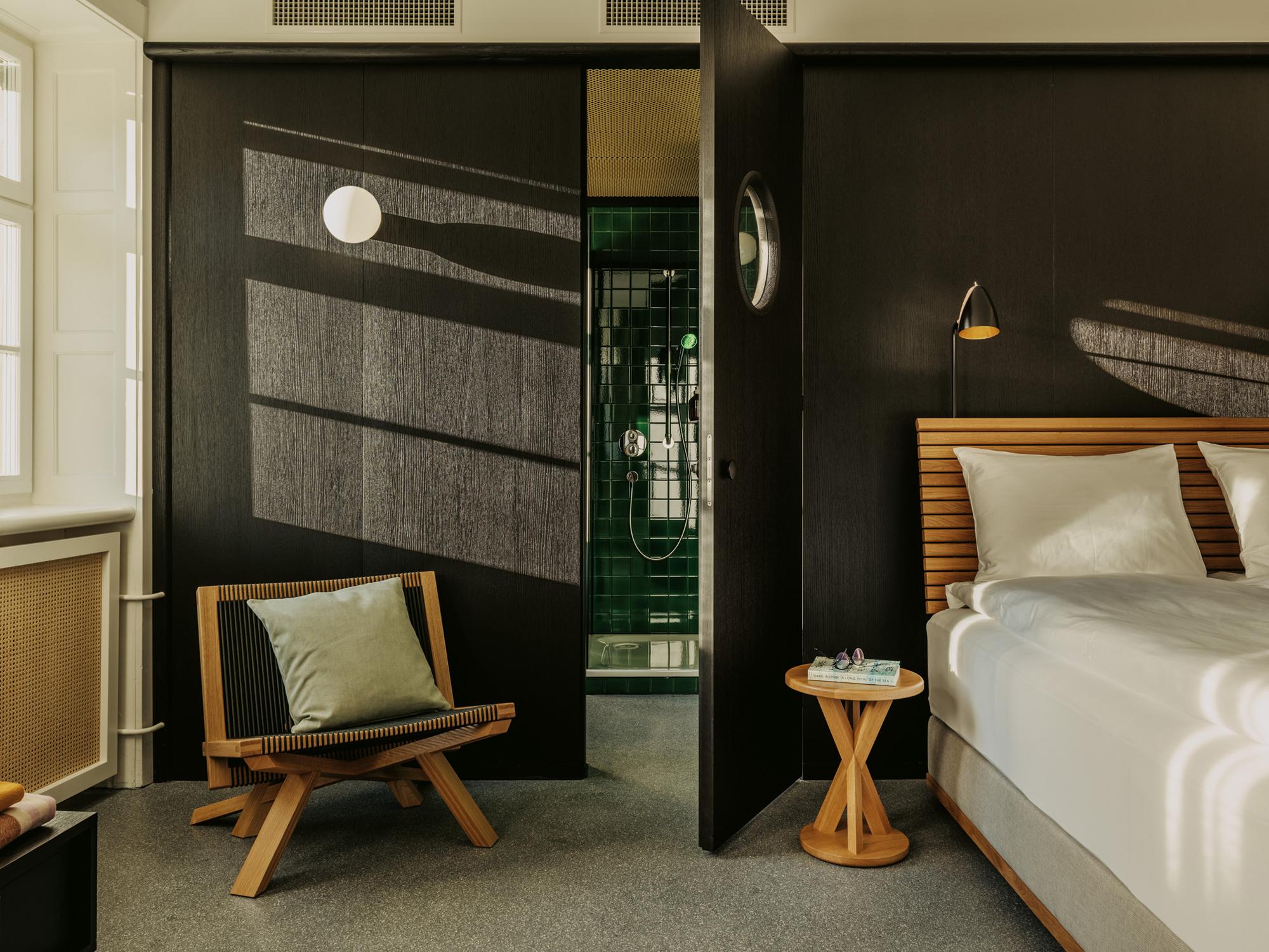 Während die Gäste in der Dusche stehen, können sie durch ovale Türöffnungen ins Zimmer und durch die dortigen Fenster hinaus ins Freie blicken.